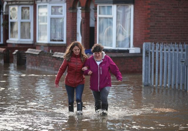 Two people walk through flood water in Doncaster
