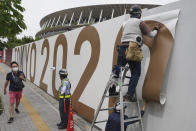 Workers paste the overlay on the wall of the National Stadium, where opening ceremony and many other events are scheduled for the postponed Tokyo 2020 Olympics, Wednesday, June 2, 2021, in Tokyo. (AP Photo/Eugene Hoshiko)