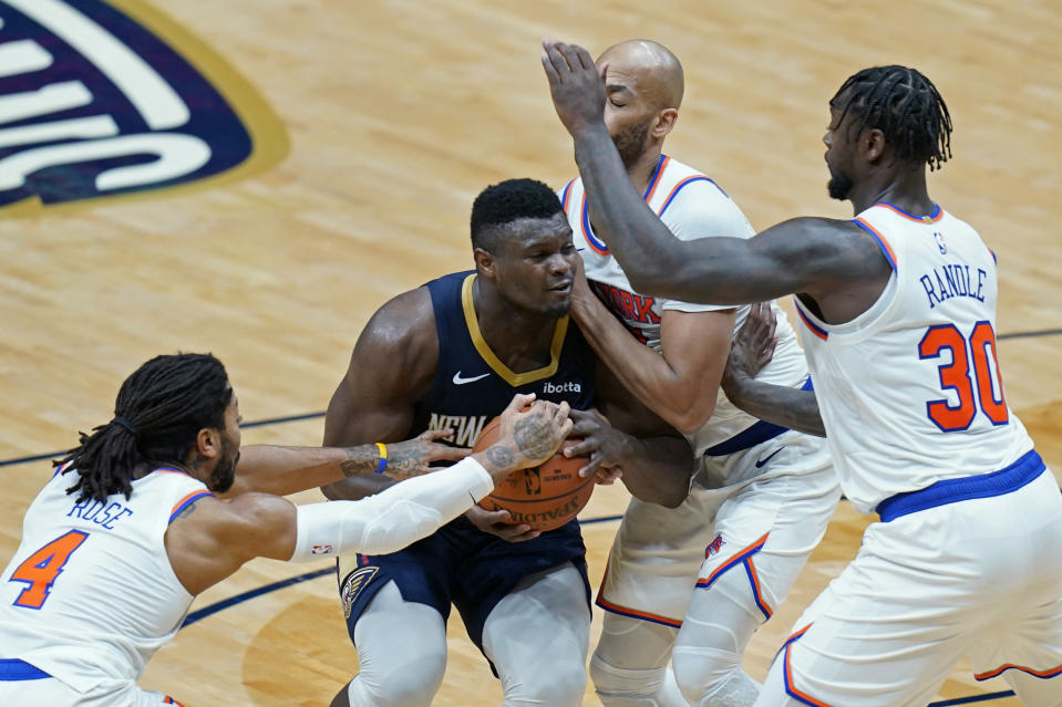 New Orleans Pelicans forward Zion Williamson is stopped by New York Knicks guard Derrick Rose (4), forward Julius Randle (30) and center Taj Gibson as he goes to the basket in the second half of an NBA basketball game in New Orleans, Wednesday, April 14, 2021. (AP Photo/Gerald Herbert)