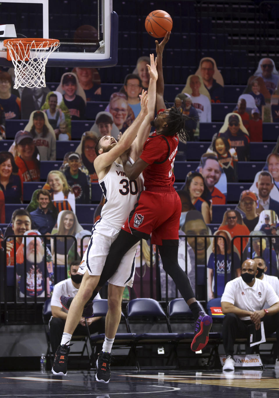 North Carolina State forward DJ Funderburk (0) is fouled by Virginia forward Jay Huff (30) during an NCAA college basketball game Wednesday, Feb. 24, 2021, in Charlottesville, Va. (Andrew Shurtleff/The Daily Progress via AP, Pool)