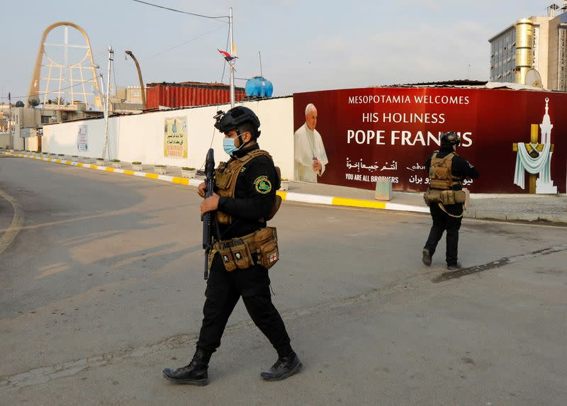Iraqi security members walk near a poster of Pope Francis ahead of his arrival, in Baghdad