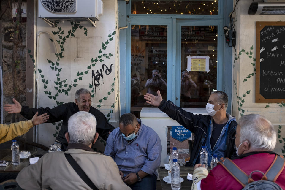 Locals chat as they sit at a traditional coffee shop in central Athens, Saturday, Oct. 31, 2020. Greece saw a jump in the number of confirmed coronavirus cases during last week, and Prime Minister Kyriakos Mitsotakis is widely expected to announce new social restrictions.(AP Photo/Yorgos Karahalis)