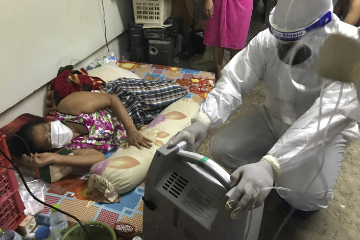A member of the volunteer Saimai Must Survive Group prepares a home oxygen concentrator to help a woman infected with the COVID-19 with difficulty breathing, late Saturday, July 24, 2021, in Bangkok, Thailand. As Thailand's medical system struggles beneath a surge of coronavirus cases, ordinary people are helping to plug the gaps, risking their own health to bring care and supplies to often terrified, exhausted patients who've fallen through the cracks. (AP Photo/Tassanee Vejpongsa)