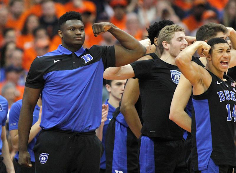 Duke's Zion Williamson, left, cheers after a basket with teammates from the bench during the second half of an NCAA college basketball game against Syracuse in Syracuse, N.Y., Saturday, Feb. 23, 2019. Duke won 75-65. (AP Photo/Nick Lisi)