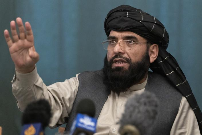 """Suhail Shaheen, member of negotiation team gestures while speaking during a joint news conference in Moscow, Russia, Friday, March 19, 2021. The Taliban warned Washington against defying a May 1 deadline for the withdrawal of American and NATO troops from Afghanistan promising a """"reaction"""". (AP Photo/Alexander Zemlianichenko, Pool)"""