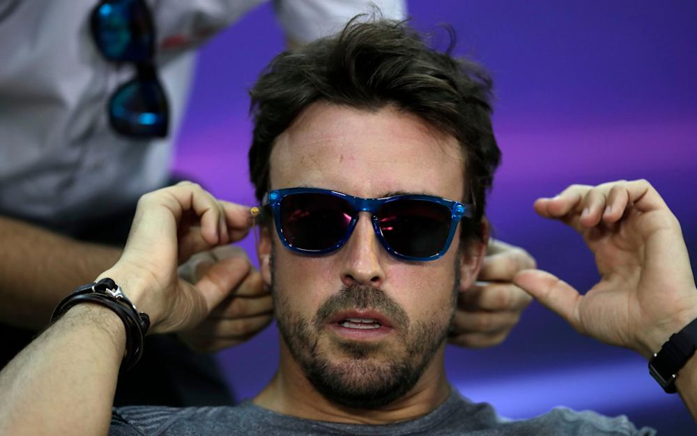 McLaren driver Fernando Alonso of Spain adjusts his earphone before the start of a news conference ahead the Bahrain Formula One Grand Prix at the Formula One Bahrain International Circuit in Sakhir, Bahrain, Thursday, April 13, 2017. The Bahrain Formula One Grand Prix will take place on Sunday. (AP Photo/Hassan Ammar) - Credit: Hassan Ammar/AP