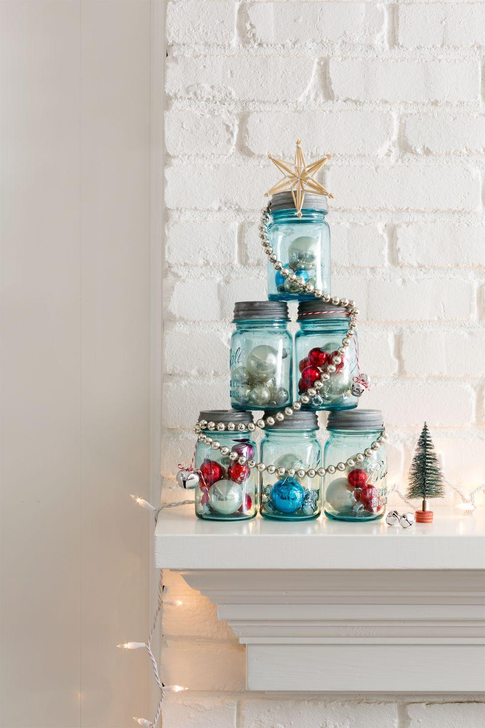 """<p>This idea's <a href=""""https://www.countryliving.com/home-design/decorating-ideas/g1571/holiday-mantels/"""" rel=""""nofollow noopener"""" target=""""_blank"""" data-ylk=""""slk:perfect for a mantel"""" class=""""link rapid-noclick-resp"""">perfect for a mantel</a> or entry table: Fill six like-sized <a href=""""https://www.amazon.com/Ball-Mouth-Elite-Collection-Quart/dp/B01AAHHBIQ/?tag=syn-yahoo-20&ascsubtag=%5Bartid%7C10050.g.2781%5Bsrc%7Cyahoo-us"""" rel=""""nofollow noopener"""" target=""""_blank"""" data-ylk=""""slk:canning jars"""" class=""""link rapid-noclick-resp"""">canning jars</a> with ornaments, tinsel, greenery, you name it. Assemble the jars in a pyramid, then wrap it with a shiny garland and top with a star. Done!</p><p><a class=""""link rapid-noclick-resp"""" href=""""https://www.amazon.com/Ball-Mouth-Elite-Collection-Quart/dp/B01AAHHBIQ/?tag=syn-yahoo-20&ascsubtag=%5Bartid%7C10050.g.2781%5Bsrc%7Cyahoo-us"""" rel=""""nofollow noopener"""" target=""""_blank"""" data-ylk=""""slk:SHOP BLUE MASON JARS"""">SHOP BLUE MASON JARS</a><br></p>"""
