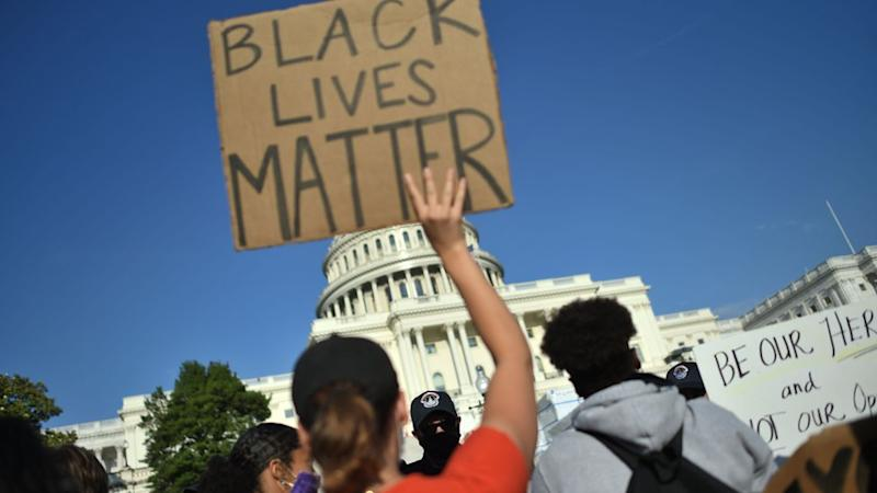 Protestors hold signs as they demonstrate in front of the United States Capitol in Washington, DC, on June 2, 2020
