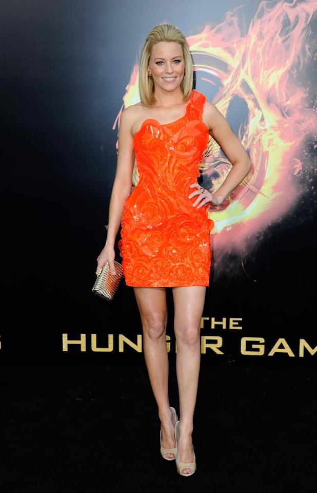 Elizabeth Banks took inspiration from her character, Effie for her asymmetric orange mini / Getty