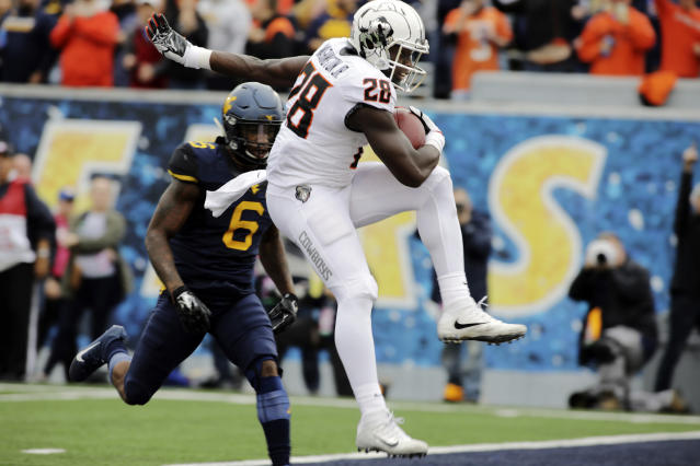 Oklahoma State wide receiver James Washington (28) runs for a touchdown while being defended by West Virginia safety Dravon Askew-Henry (6) during the first half of an NCAA college football game, Saturday, Oct. 28, 2017, in Morgantown, W.Va. (AP Photo/Raymond Thompson)