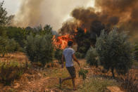 A man walks toward wildfires in Kacarlar village near the Mediterranean coastal town of Manavgat, Antalya, Turkey, Saturday, July 31, 2021. The death toll from wildfires raging in Turkey's Mediterranean towns rose to six Saturday after two forest workers were killed, the country's health minister said. Fires across Turkey since Wednesday burned down forests, encroaching on villages and tourist destinations and forcing people to evacuate. (AP Photo)