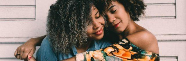 Two black women with natural, curly hair, one with her arms around the other