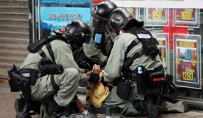 Riot police subdue an anti-government protester at march in Hong Kong's Tai Po district on March 8. Photo: Dickson Lee
