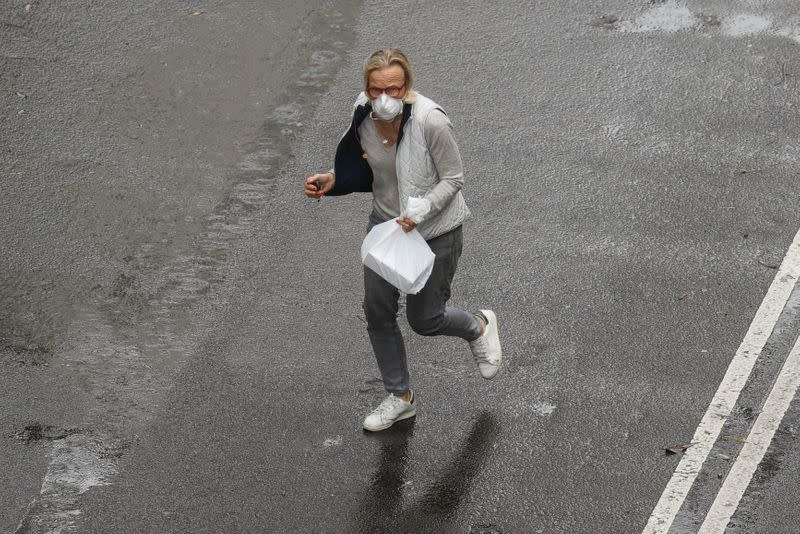 A pedestrian wears a mask while crossing a street in Sydney