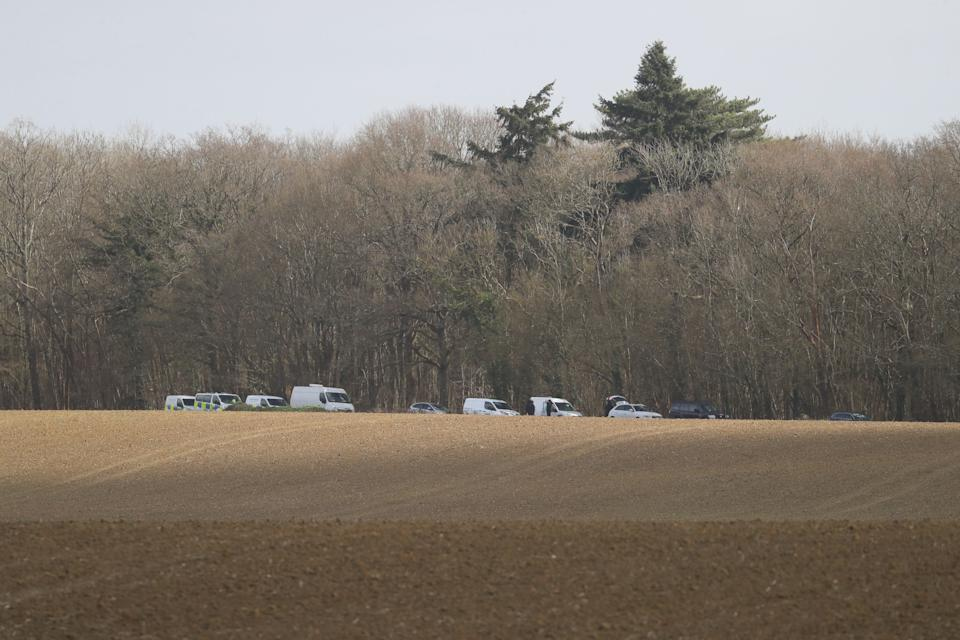 Police and forensic officers conduct a search in an area of woodland in Ashford. (PA)
