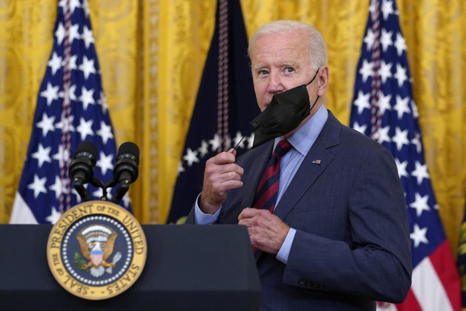 President Joe Biden takes off his mask as he arrives to speak about the coronavirus pandemic in the East Room of the White House in Washington, Tuesday, Aug. 3, 2021. The U.S. has donated and shipped more than 110 million doses of COVID-19 vaccines to more than 60 countries, ranging from Afghanistan to Zambia, the White House announced Tuesday. (AP Photo/Susan Walsh)