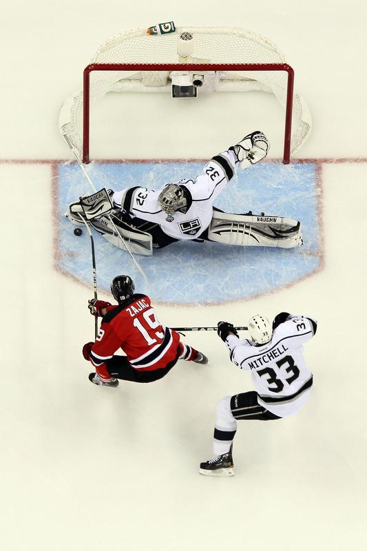 NEWARK, NJ - JUNE 09: Jonathan Quick #32 of the Los Angeles Kings makes a save in front of Travis Zajac #19 of the New Jersey Devils and Willie Mitchell #33 during Game Five of the 2012 NHL Stanley Cup Final at the Prudential Center on June 9, 2012 in Newark, New Jersey. (Photo by Jim McIsaac/Getty Images)