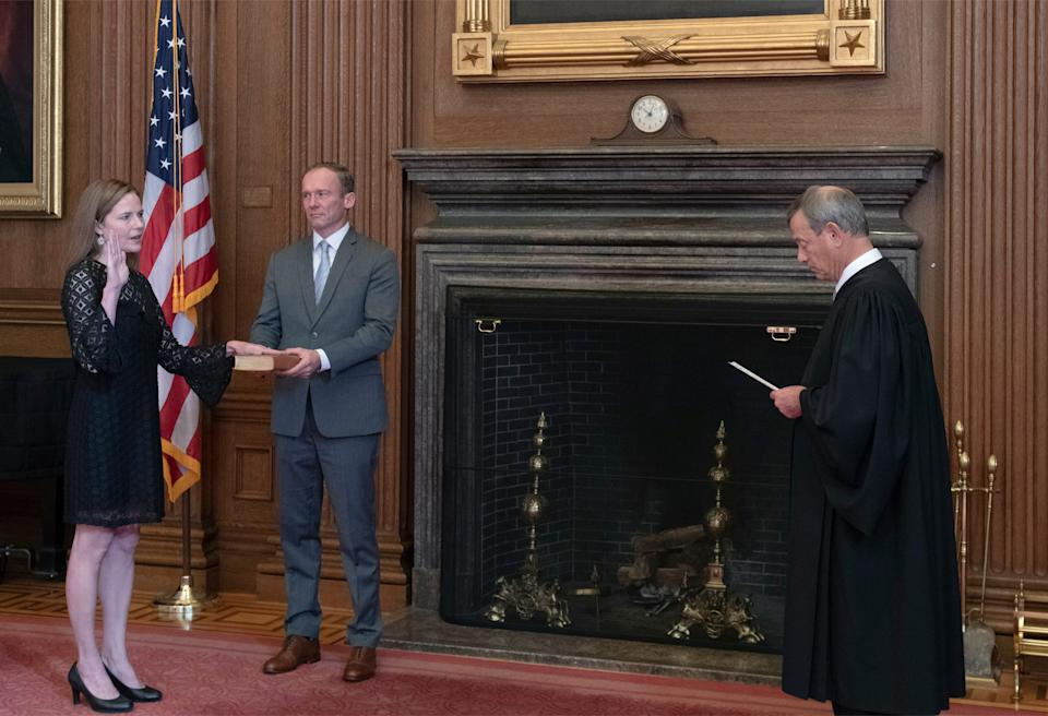 Chief Justice John Roberts administers the judicial oath to Amy Coney Barrett, joined by Barrett's husband, Jesse Barrett, in a private ceremony in the Supreme Court building early Tuesday.