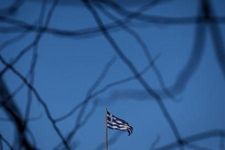 A Greek national flag flutters on the roof of a building in Athens