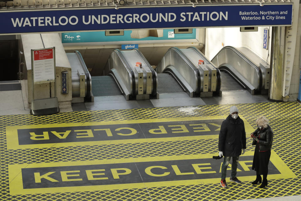FILE - In this Tuesday, March 24, 2020 file photo, two people wearing masks stand at the top of a bank of escalators in London's Waterloo Station. British Prime Minister Boris Johnson is expected to confirm Monday June 14, 2021, that the next planned relaxation of coronavirus restrictions in England will be delayed as a result of the spread of the delta variant first identified in India. (AP Photo/Matt Dunham, File)