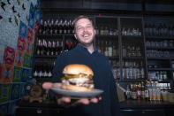 Josh Phillips, the co-owner of Espita, a stylish Mexican restaurant, holds a Ghostburger at his restaurant in downtown Washington, Monday, Feb. 15, 2021. Phillips opened a delivery-only brand called Ghostburger in August to keep Espita's kitchen running through the winter. He chose burgers because he wanted to reach new customers at a lower price point than Espita. It's been so successful that Phillips is now scouting for locations for standalone Ghostburger restaurants. (AP Photo/Jose Luis Magana)