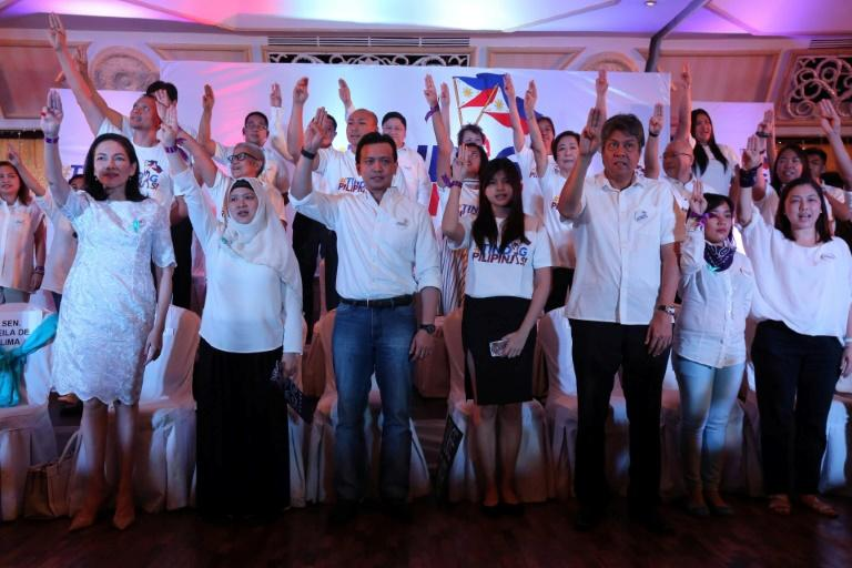 Philippine Senators Risa Hontiveros (L), Antonio Trillanes (3rd L), Francis Pangilinan (3rd R) and others raising a three-finger salute, as they launched the Tindig Pilipinas (Arise Philippines) movement in Manila