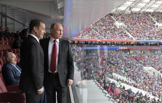 Russian President Vladimir Putin, right, and Russian Prime Minister Dmitry Medvedev look at the field during the match between Russia and Saudi Arabia which opens the 2018 soccer World Cup, at the Luzhniki stadium in Moscow, Russia, Thursday, June 14, 2018. Belarusian President Alexander Lukashenko, is seen behind them on the left. (Alexei Druzhinin, Sputnik, Kremlin Pool Photo via AP)