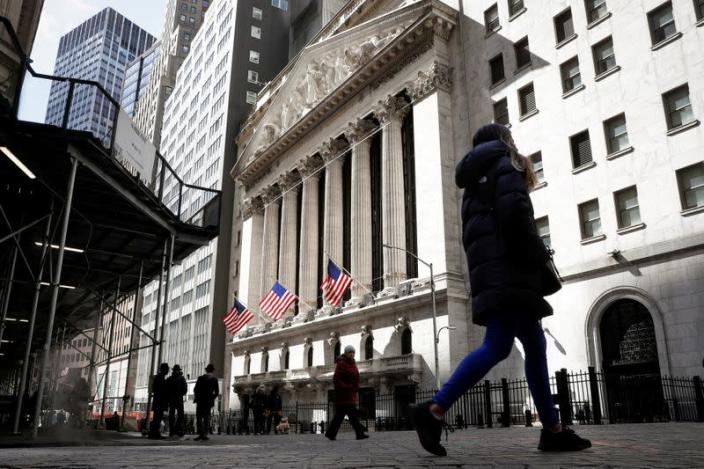 FILE PHOTO: People are seen on Wall St. outside the NYSE in New York