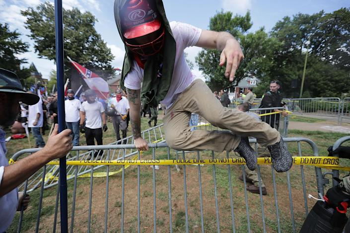"""<p>White nationalists, neo-Nazis and members of the """"alt-right"""" leap over barricades inside Lee Park during the """"Unite the Right"""" rally Aug. 12, 2017 in Charlottesville, Va. (Photo: Chip Somodevilla/Getty Images) </p>"""