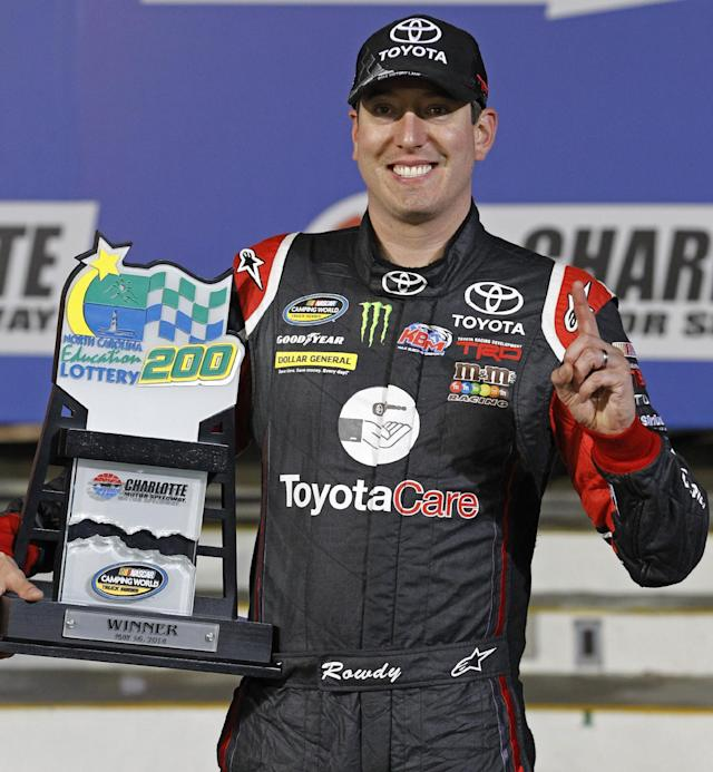 Kyle Busch poses with the trophy in Victory Lane after winning the NASCAR Trucks series auto race at Charlotte Motor Speedway in Concord, N.C., Friday, May 16, 2014. (AP Photo/Terry Renna)
