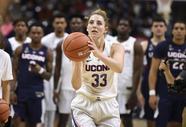FILE - In this Friday, Oct. 12, 2018 file photo,Connecticut's Katie Lou Samuelson prepare to throw a three-point basket in a contest as the UConn's men's and women's NCAA college basketball teams look on during the annual First Night celebration in Storrs, Conn. (AP Photo/Jessica Hill, File)
