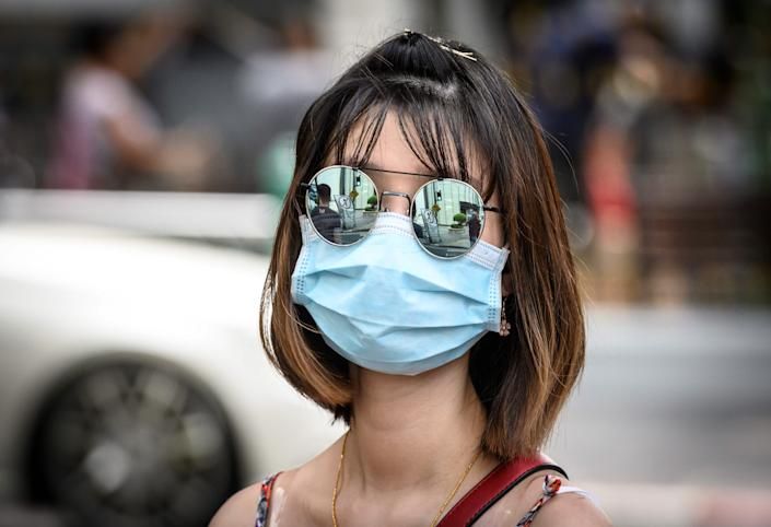 A woman wearing a protective facemask walks on a street in Bangkok on February 13, 2020. (Photo by Mladen ANTONOV / AFP) (Photo by MLADEN ANTONOV/AFP via Getty Images)