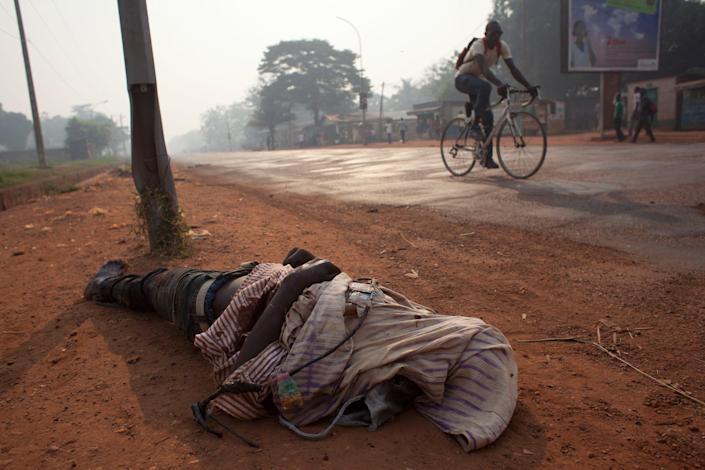 A man cycles past the body of a man draped in a string of protective charms typical of the anti-balaka Christian militiamen, in the mainly Muslim Combatant neighborhood of Bangui, Central African Republic, Tuesday, Dec. 24, 2013. Sectarian violence continues to claim victims daily in Central African Republic's tense capital city. (AP Photo/Rebecca Blackwell)