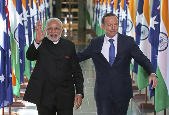 """FILE - In this Nov. 18, 2014, file photo, India's Prime Minister Narendra Modi, left, waves as he is escorted by Australian Prime Minister Tony Abbott as they leave the House of Representatives at Parliament House in Canberra, Australia. An India-Australia free trade agreement would signal the """"democratic world's tilt away from China,"""" trade envoy and former Australian Prime Minister Tony Abbott has written on Monday, Aug. 9, 2021. (AP Photo/Rick Rycroft, Pool, File)"""