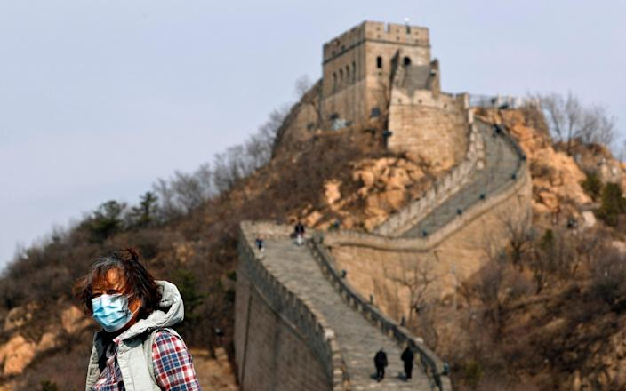 A woman wearing a protective face mask visits the Badaling Great Wall of China after it reopened for business following the new coronavirus outbreak in Beijing - AP