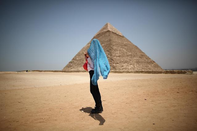 CAIRO, EGYPT - MAY 28: A tourist covers her head against the sun in sight of the Pyramid of Chephren on May 28, 2011 in Giza, Egypt. Protests in January and February brought an end to 30 years of autocratic rule by President Hosni Mubarak who will now face trial. Food prices have doubled and youth unemployment stands at 30%. Tourism is yet to return to pre-uprising levels. (Photo by Peter Macdiarmid/Getty Images)