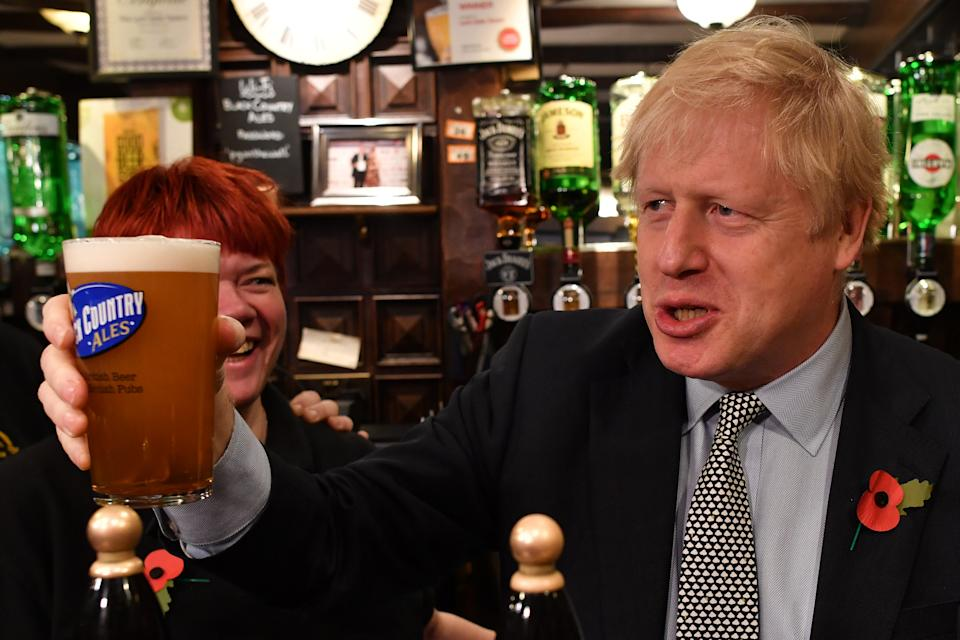 WOLVERHAMPTON, UNITED KINGDOM - NOVEMBER 11: British Prime Minister Boris Johnson raises a pint of beer as he campaigns ahead of the general election at the Lynch Gate Tavern on November 11, 2019 in Wolverhampton, United Kingdom. The U.K. will go to the polls in a general election on December 12. (Photo by Ben Stansall – WPA Pool/Getty Images)