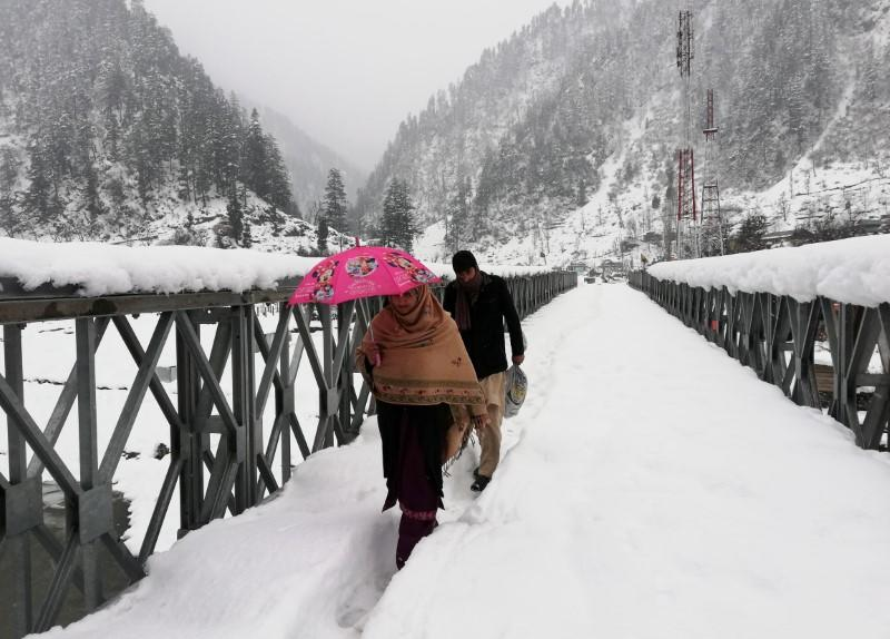 People walk on a snow-covered bridge after a heavy snowfall in Neelum Valley
