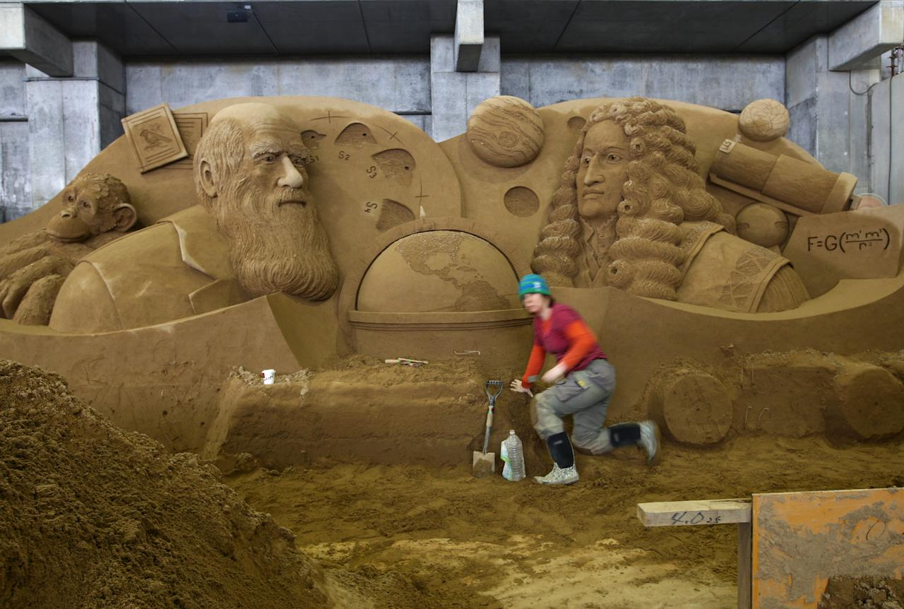 Karen Fralich of Canada finishes a sand replica titled 'British Science Legend of Sir Isaac Newton & Charles Robert Darwin' at Sand Museum located in the Tottori Dune on April 1, 2012 in Tottori, Japan. (Photo by Buddhika Weerasinghe/Getty Images)