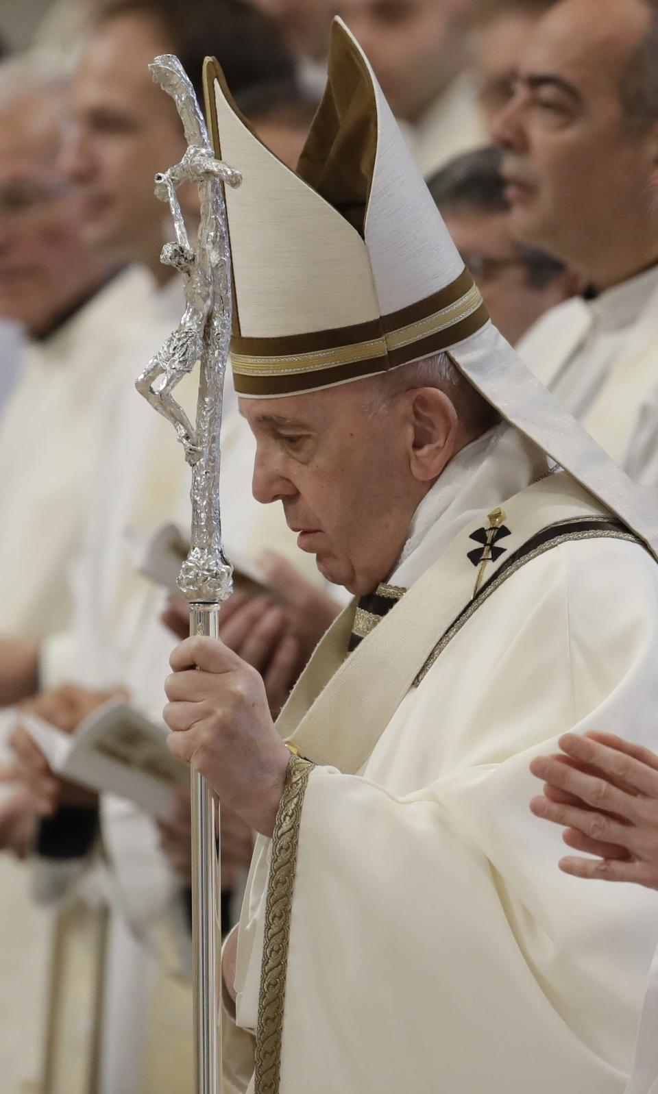 Pope Francis holds his pastoral staff as he arrives to celebrate Chrism Mass, inside St. Peter's Basilica, at the Vatican, Thursday, April 18, 2019. During the Mass the Pontiff blesses a token amount of oil that will be used to administer the sacraments for the year. (AP Photo/Alessandra Tarantino)