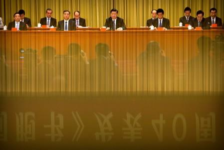 """FILE PHOTO: A banner is reflected on a polished surface as Chinese President Xi Jinping (C) speaks during an event to commemorate the 40th anniversary of the """"Message to Compatriots in Taiwan"""" at the Great Hall of the People in Beijing"""