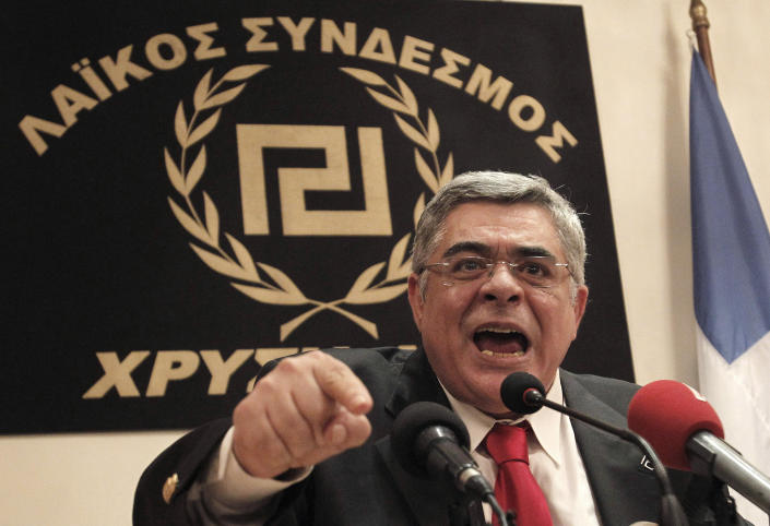FILE - In this May 6, 2012 file photo, extreme right Golden Dawn party leader Nikos Mihaloliakos speaks during a news conference in front of a banner with the twisting Maeander, an ancient Greek decorative motif that the party has adopted as its symbol, in Athens. Greek police said Mihaloliakos was arrested on charges of forming a criminal organization. Warrants for the arrest of another five Golden Dawn parliament deputies have been issued. The police counterterrorism unit is looking for the deputies. More warrants are expected. (AP Photo/Petros Giannakourism, File)
