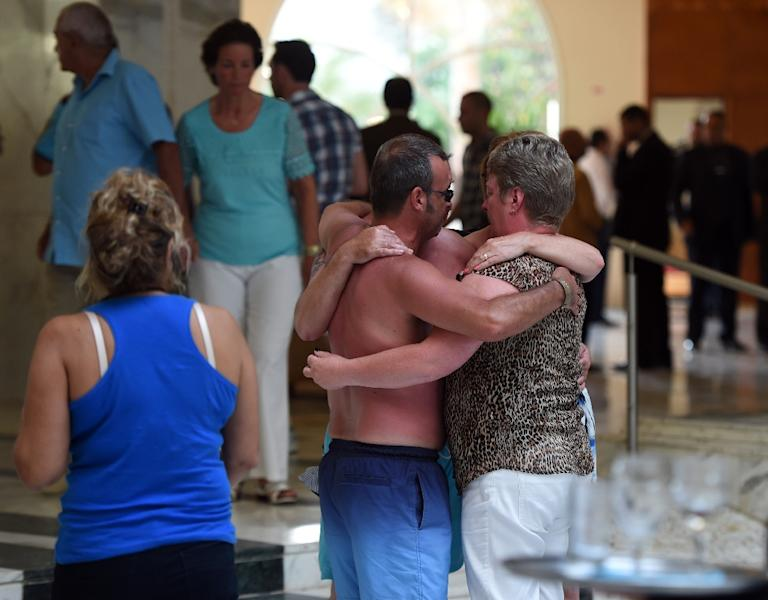 Tourists comfort each other after a mass shooting attack in the resort town of Sousse, a popular tourist destination 140 km south of the Tunisian capital, on June 26, 2015 (AFP Photo/Fethi Belaid)