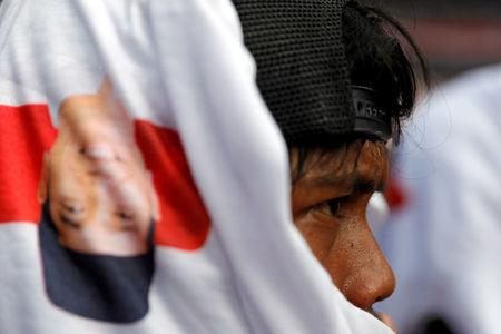A supporter covers his head with a T-shirt with the image of Indonesia's incumbent presidential candidate Joko Widodo during a campaign rally at Gelora Bung Karno stadium in Jakarta