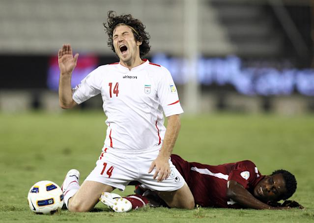 FILE - In this Sept, 6, 2011, file photo, Qatar's Lawrence Quaye, right,fights the ball against Iran's Anderanik Teymourian during their 2014 World Cup Asian qualifying football match at Al-Sadd Stadium in Doha. (AP Photo/Osama Faisal,File )