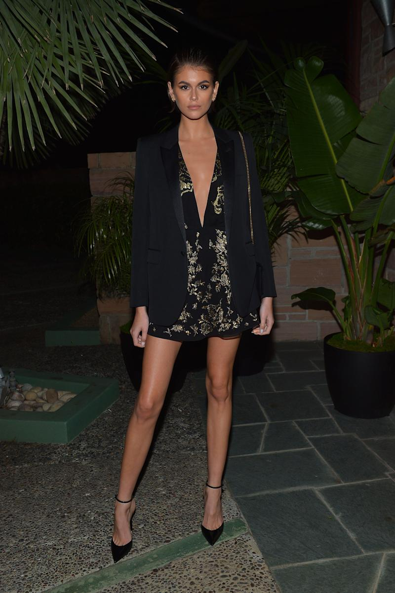 Kaia Gerber looks smashingly hot in low-cut black dress with gold designs and a black jacket to match.