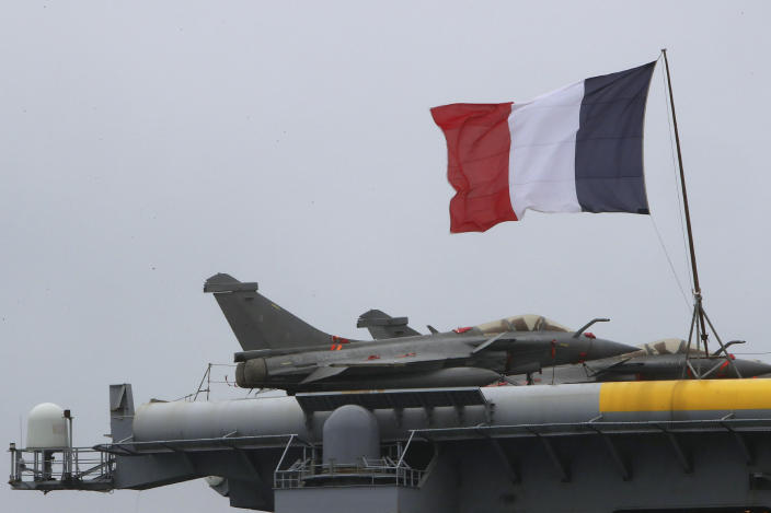 FILE - In this Friday, Feb. 21, 2020 file photo, a French flag flies near Rafale warplanes on the deck of the aircraft carrier Charles de Gaulle, docked at Cyprus' main port of Limassol. Greece's government says on Thursday, Dec. 17, 2020, it will pay 2.32 billion euros ($2.8 billion) for the purchase of French-made Rafale fighter jets and an upgrade of compatible air-to-air missile systems and part of a major military overhaul. (AP Photo/Petros Karadjias, File)