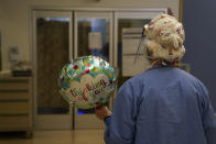 Registered nurse Anita Grohmann carries a balloon delivered to a patient in a COVID-19 unit at St. Joseph Hospital in Orange, Calif. Thursday, Jan. 7, 2021. The state's hospitals are trying to prepare for the possibility that they may have to ration care for lack of staff and beds — and hoping they don't have to make that choice as many hospitals strain under unprecedented caseloads. (AP Photo/Jae C. Hong)