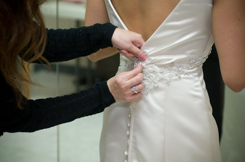A bride getting ready before wedding. She is having help with her dress.