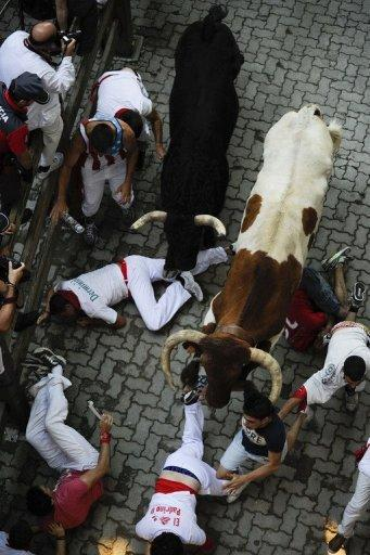 <p>Participants fall in front of bulls during the third bull run of the San Fermin Festival in Pamplona, northern Spain, on July 9, 2013. At least two people were injured as thrill-seekers tumbled into each other in a desperate scramble to escape six half-tonne fighting bulls thundering through the cobbled streets of Pamplona.</p>